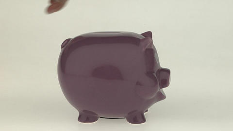 A woman's hand puts a coin into a pink piggy bank Footage