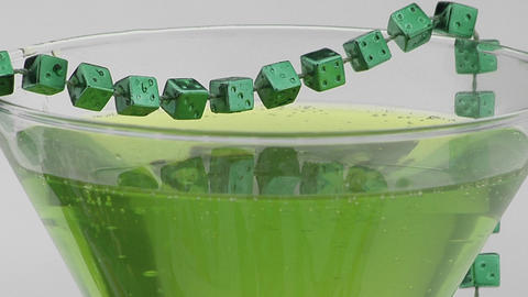 Beads of green dice adorn a cocktail glass Stock Video Footage
