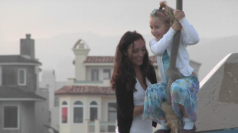 A woman helps a girl ride a zip line Stock Video Footage