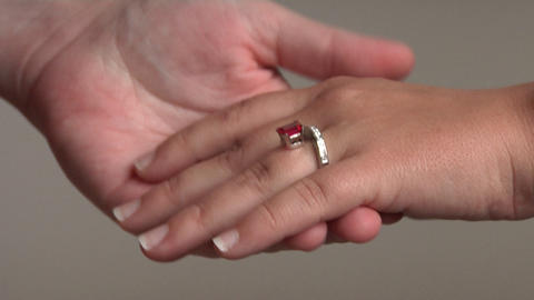 A man puts a gemstone ring on a woman's hand Stock Video Footage