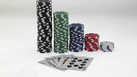 Stacks of poker chips sit in a row, arranged by value behind a deck of playing cards Footage