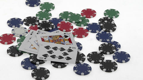 A poker player throws down his winning hand of cards then gathers a pile of polar chips Footage