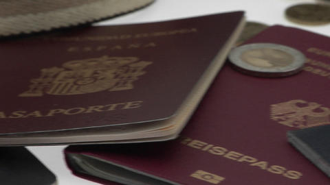Passports and coins are displayed on a white surface Footage
