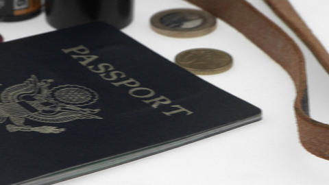 Passports and coins are displayed on a white surface Stock Video Footage