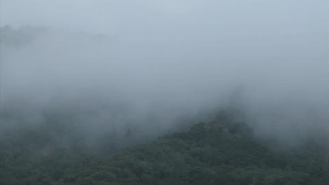 Fog rolls across a mountaintop Stock Video Footage