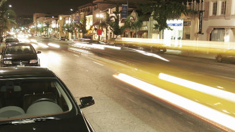 Cars speed along city streets at night Stock Video Footage