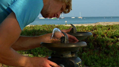 A man sips water at a drink fountain Stock Video Footage