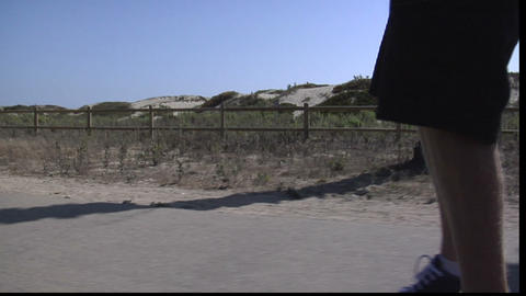 A skateboarder maneuvers his way along a seaside sidewalk Stock Video Footage