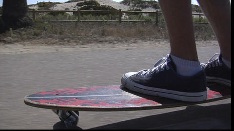 A skateboarder maneuvers his way along a seaside sidewalk Stock Video Footage