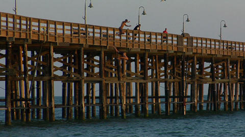 young men jump from a pier into the sea Footage