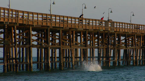 young men jump from a pier into the sea Stock Video Footage