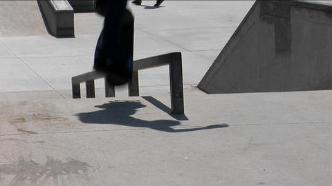 A skateboarder ollies onto a rail and grinds his way down Stock Video Footage