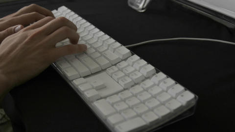 Hands type rapidly on a white keyboard Footage