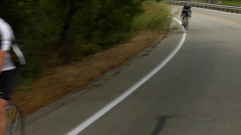 Bicyclists pedal around a mountain curve Stock Video Footage