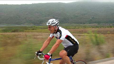 A bicyclist pants and grimaces as he peddles along a highway Footage