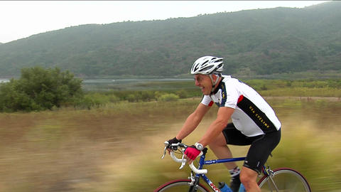 A bicyclist pants and grimaces as he peddles along a highway Stock Video Footage