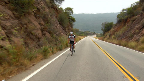 A bicyclist peddles along a highway in a mountainous area Stock Video Footage
