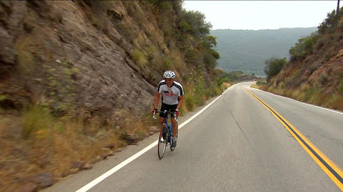 A bicyclist peddles along a highway in a mountainous area Footage