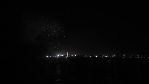 Fireworks explode over calm waters in the sky Stock Video Footage