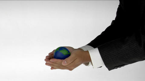 A pair of cupped hands hold a small globe Footage