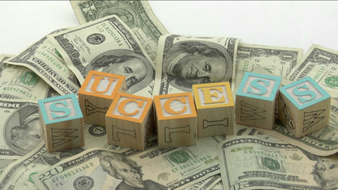 "Arranged wood blocks spell out the word success"" on top of a pile of paper currency Footage"