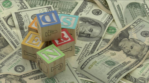 wooden alphabet blocks sit on top of a pile of money Footage