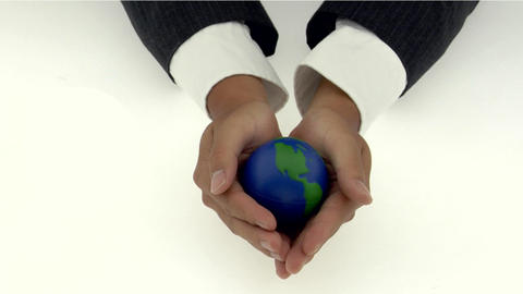 A pair of cupped hands holds a small globe Footage