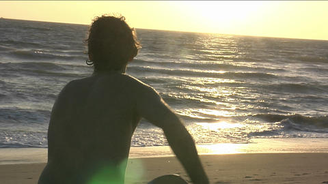 A man runs towards the ocean with a body board Footage