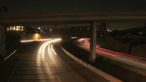 Vehicle headlights shine on a freeway at night Stock Video Footage