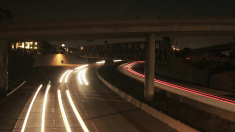 Vehicle headlights shine on a freeway at night Footage