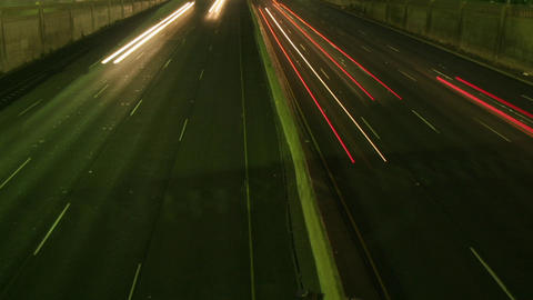 A slow tilt up reveals traffic move at light speed along... Stock Video Footage