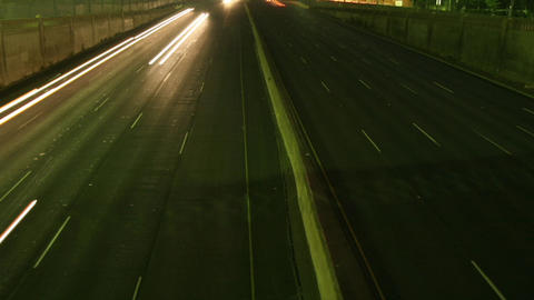 A slow tilt up reveals traffic move at light speed along a freeway in this time lapse shot Footage