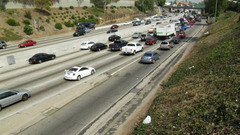 Traffic moves slowly along a busy freeway Stock Video Footage