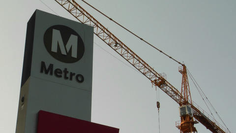 A construction crane stands behind a sign indicating the... Stock Video Footage