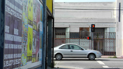Traffic drives through an area of rundown storefronts Stock Video Footage