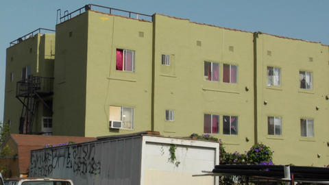 A green apartment building rises along a neighborhood street Stock Video Footage