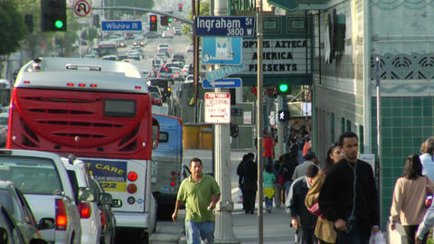 Traffic passes pedestrians and stores on a city street Stock Video Footage