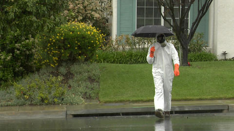 A man in a hazmat suit holds an umbrella and crosses the... Stock Video Footage
