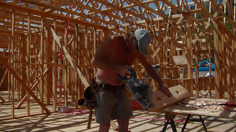 A contractor cuts a piece of wood, then puts it into place Stock Video Footage