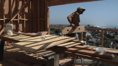 A contractor hammers at a piece of wood and carries it away Stock Video Footage