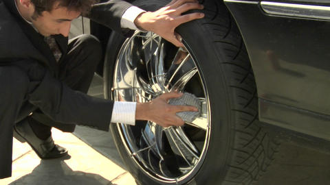 A man wearing a suit polishes a tire rim Footage