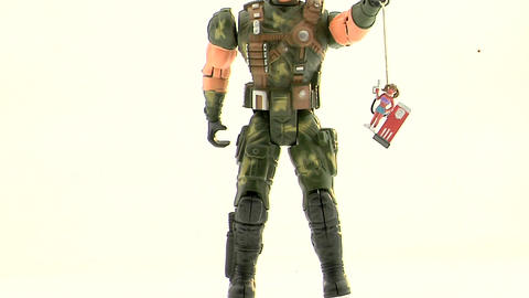 An Army action figure holds a plastic figurine of a woman at a gas pump by a string Footage