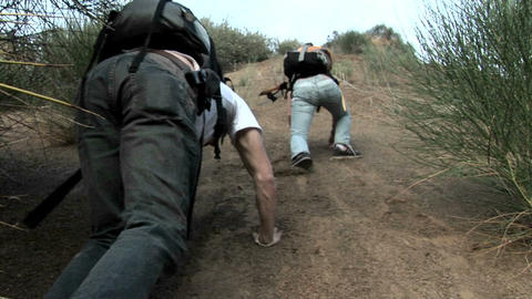 A woman and man wearing backpacks struggle to climb up a hillside of loose dirt Footage