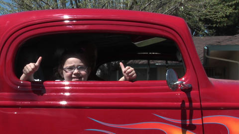 A young girl gives two thumbs up out a car window Footage
