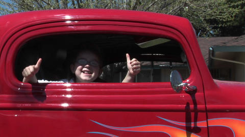 A young girl gives two thumbs up out a car window Stock Video Footage