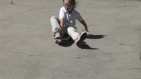 A young girl rides a skateboard and a boy rides a plastic... Stock Video Footage
