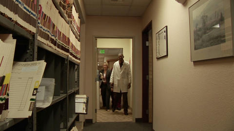 Medical personnel walk through a hallway Stock Video Footage