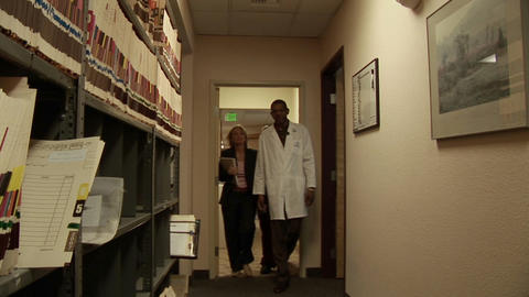 Medical personnel walk through a hallway Footage