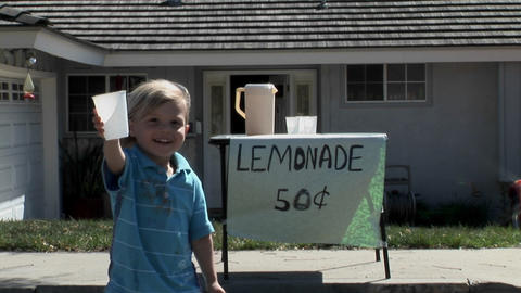 A boy offers a cup at a lemonade stand Stock Video Footage