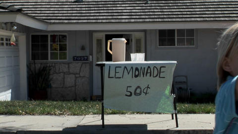 A boy offers a cup at a lemonade stand Live Action